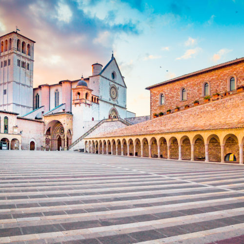 Famous Basilica of St. Francis of Assisi (Basilica Papale di San Francesco) with Lower Plaza at sunset in Assisi, Umbria, Italy